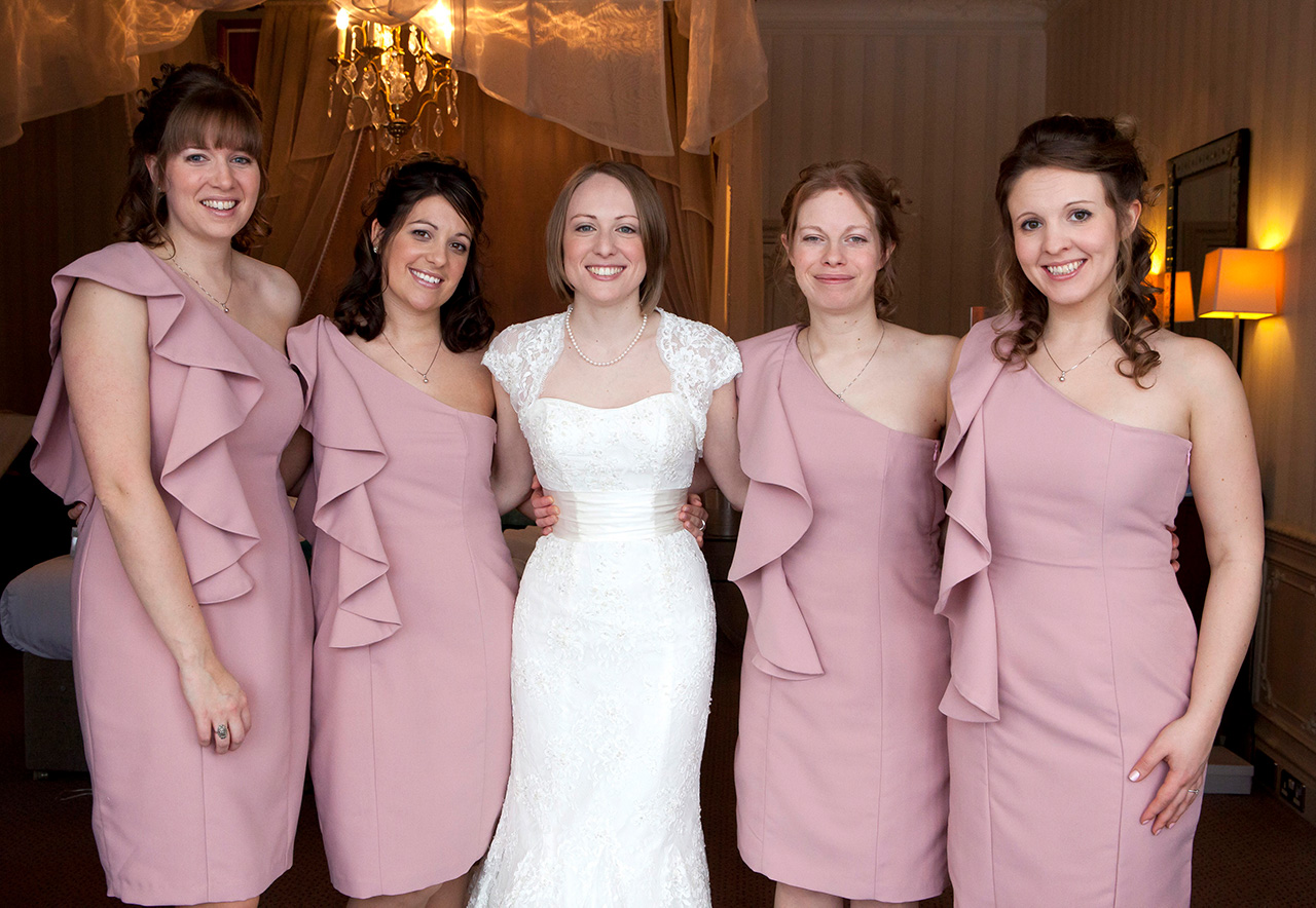 Bride wearing dress with bridesmaids